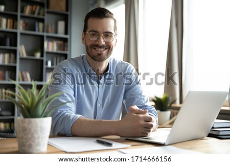 Head shot portrait smiling businessman wearing glasses sitting at work desk with laptop, looking at camera, confident satisfied man freelancer student posing for photo at workplace with computer Royalty-Free Stock Photo #1714666156