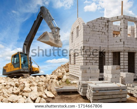 Demolition. Crawler Excavator. Concept - the demolition of illegal house. Crawler excavator demolishes an unfinished house. Excavator at a construction site. Unfinished house on the background of sky #1714667806