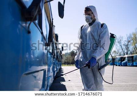 Public transport disinfection. Man in white protective suit with reservoir spraying disinfectant on parked buses. Stop coronavirus or COVID-19. #1714676071
