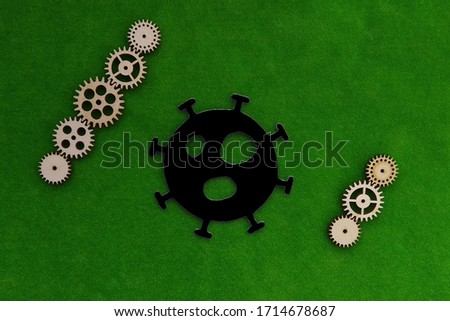 The virus sign is black, with wooden gears on a green background. The mechanism of spread of the virus, a pandemic. #1714678687