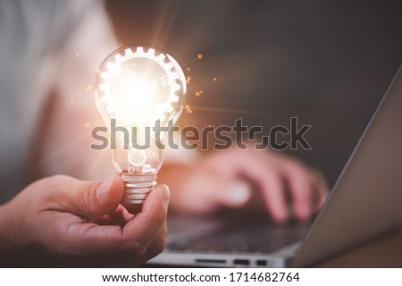 The hand of a man with a light bulb And there is a gear icon in it And he is using a notebook computer. The idea of inspiration from online technology.innovation idea concept. #1714682764