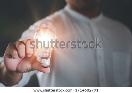 Businessman holding a bright light bulb. Concept of Ideas for presenting new ideas Great inspiration and innovation new beginning. Royalty-Free Stock Photo #1714682791