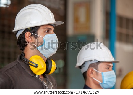 Workers wear protective face masks for safety in machine industrial factory. #1714691329