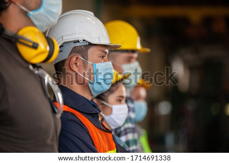 Workers wear protective face masks for safety in machine industrial factory. #1714691338