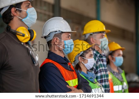 Workers wear protective face masks for safety in machine industrial factory. #1714691344
