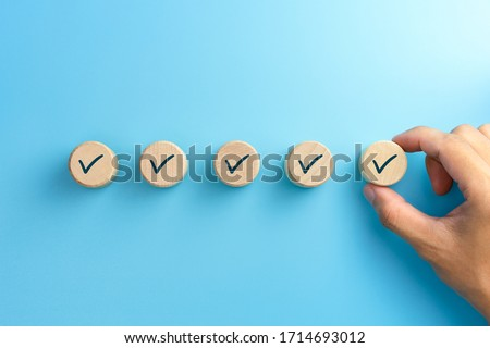 Checklist concept, Check mark on wooden blocks, blue background with copy space Royalty-Free Stock Photo #1714693012