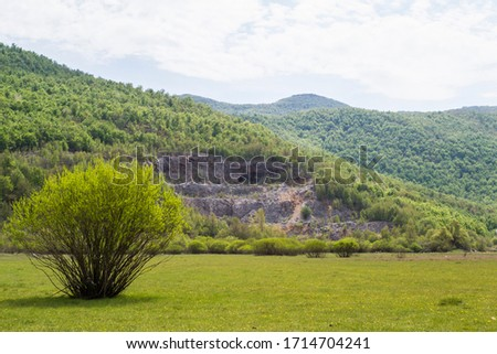 Velebit mountains and abandoned stone quarry in springtime as seen from Gracac field, Croatia #1714704241