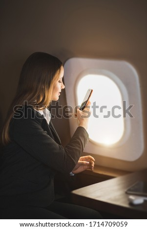 Adorable caucasian girl traveling by private airplane. Charming brown haired young woman sitting by aircraft window and taking pictures of sky on her smartphone. Flying first class.