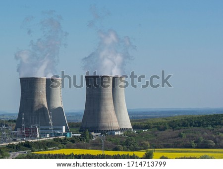 Cooling towers of nuclear power plant Mochovce with the yellow field of rapeseed in front of them. Royalty-Free Stock Photo #1714713799