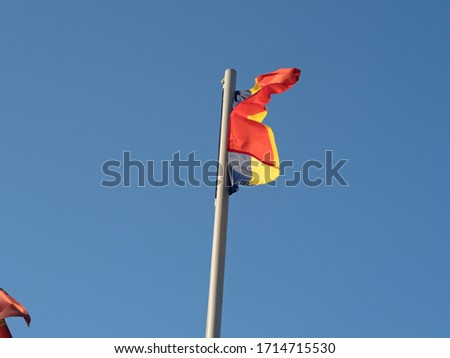 belgian flag on a pole against blue sky  #1714715530