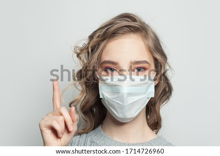 Young woman wearing a face mask on gray background. Woman in medical mask. Flu epidemic and virus protection concept #1714726960