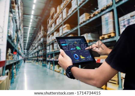 Smart warehouse management system.Worker hands holding tablet on blurred warehouse as background Royalty-Free Stock Photo #1714734415