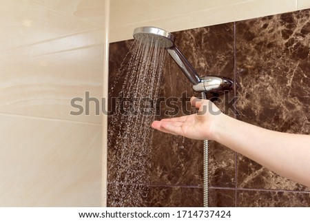 Running water of shower faucet. Woman's hand held under shower water #1714737424