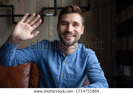 Headshot portrait of happy Caucasian young man sit in cafe wave greeting talking on video call, smiling millennial male have fun speaking online using gadget engaged in internet dating service Royalty-Free Stock Photo #1714751884