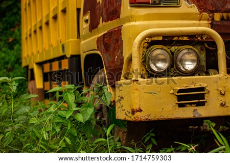 An Indonesian dump truck abandoned in the jungle. Close up. Car on the background of a green forest. Rusty cab of the vehicle. Left side of the car cab and body. #1714759303