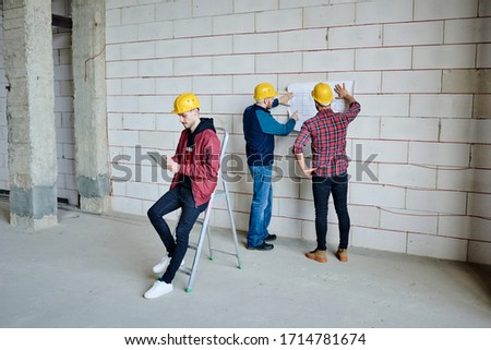 Young engineer in hardhat sitting on stepladder and scrolling through description of building materials with his colleagues on background #1714781674