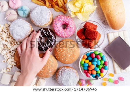 Fast food concept. Unhealthy food. Unhealthy food and fast food with donuts, chocolate, burgers and sweets top view #1714786945