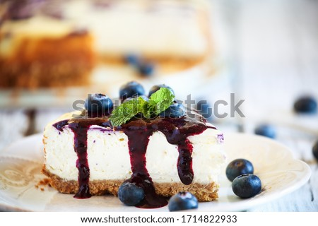A slice of delicious homemade blueberry marble cheesecake with graham cracker crust, blueberry sauce and fresh blueberries. Selective focus with extreme shallow depth of field.
