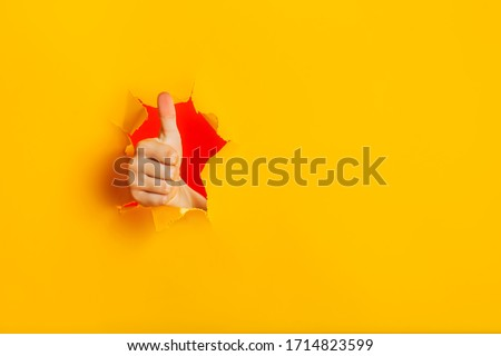 Female child hand gesturing the ok sign, like gesture through torn yellow paper wall, keeps thumb up. Approval sign, recommends something. Copy space fo text information. Best choice concept. #1714823599