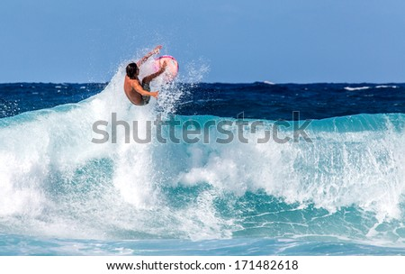 Surfer jumping above a wave on the North Shore of Oahu, Hawaii Royalty-Free Stock Photo #171482618