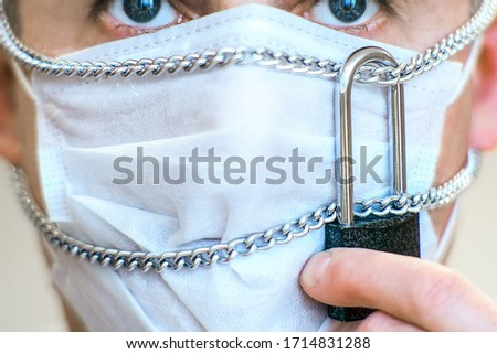 A mask on a person's face, chained and padlocked. The concept of primary protection against the spread of coronavirus. Be sure to wear the mask yourself and insist that your neighbors wear it. #1714831288