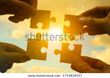 Four hands of businessmen assemble pieces of a puzzle into a single whole against the backdrop of the sunset, business concept idea, partnership, teamwork, cooperation, creative Royalty-Free Stock Photo #1714834927
