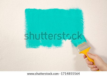 Man with Yellow brush painting the wall with green color  #1714855564