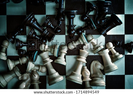 Chess pieces are scattered on the chessboard, the picture is in dark style, low key. The concept of the lost game in the style of horror