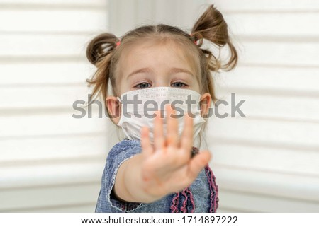 little girl in a disposable mask showing stop gesture with palm looking straight at camera. Covid 19, the concept of coronavirus. #1714897222