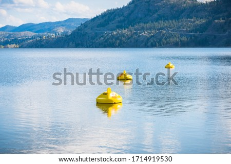 Yellow buoys marking hazardous area with dangerous under currents on lake, where swimming is not permitted Royalty-Free Stock Photo #1714919530
