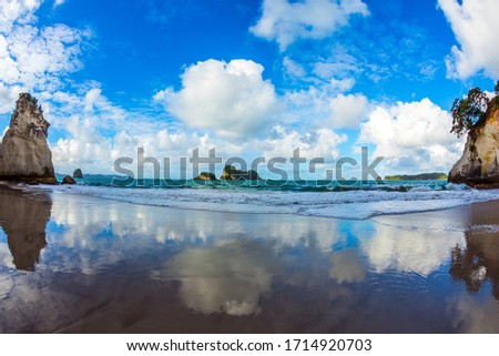 The far end of the earth. Travel to New Zealand. Ocean tidal wave in the Cathedral Cove. Mirror reflections of clouds in wet sand. The concept of exotic, ecological and photo tourism