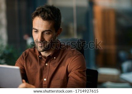 Smiling businessman sitting after hours at his desk in a dark office and working online with a digital tablet #1714927615