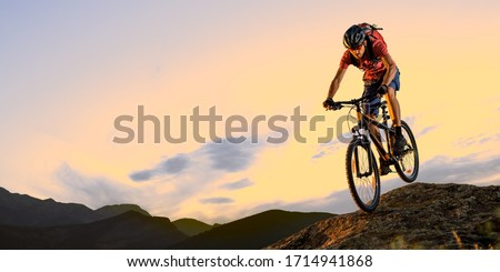 Cyclist in Red Riding the Bike Down the Rock in the Beautiful Mountains on the Sunset. Extreme Sport and Enduro Biking Concept. #1714941868