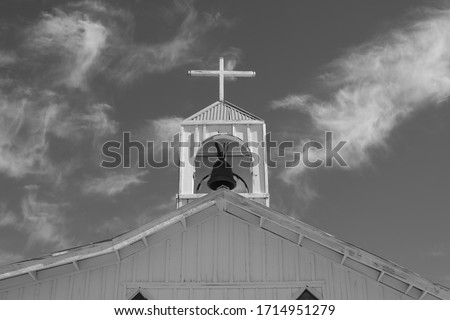 Close up of a Black and white picture of an old church with a bell tower .