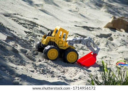 a plastic children excavator toy in a sand #1714956172