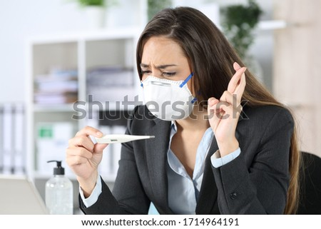 Worried executive woman with protective mask looking at thermometer result crossing fingers at the office #1714964191