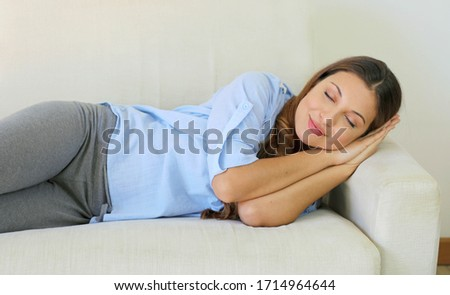 Beautiful girl napping relaxing on a comfortable couch at home #1714964644