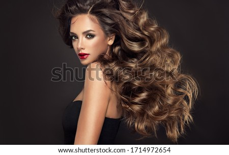 Beautiful model girl with long wavy and shiny hair . Brunette woman with curly hairstyle and red lips  Royalty-Free Stock Photo #1714972654