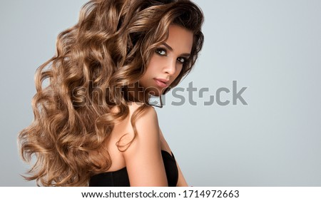 Beautiful model girl with long wavy and shiny hair . Brunette woman with curly hairstyle  Royalty-Free Stock Photo #1714972663