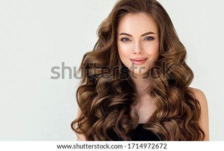 Beautiful laughing brunette model  girl  with long curly  hair . Smiling  woman hairstyle wavy curls . Red  nails manicure .    Fashion , beauty and makeup portrait  Royalty-Free Stock Photo #1714972672