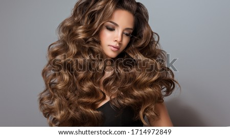 Beautiful model girl with long wavy and shiny hair . Brunette woman with curly hairstyle  Royalty-Free Stock Photo #1714972849