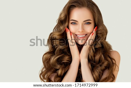 Beautiful laughing brunette model  girl  with long curly  hair . Smiling  woman hairstyle wavy curls . Red  nails manicure .    Fashion , beauty and makeup portrait  Royalty-Free Stock Photo #1714972999