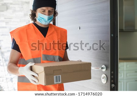 Young delivery man at front door with a parcel box, wearing gloves and face mask during covid-19 pandemic lockdown. Copy space.