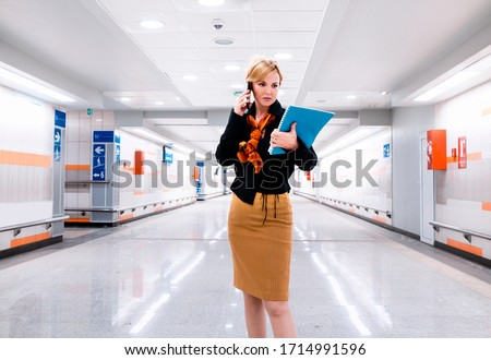 Busy Woman CEO manager in hall of business building using phone and checking document file.Business Woman in modern hallaway going to work #1714991596