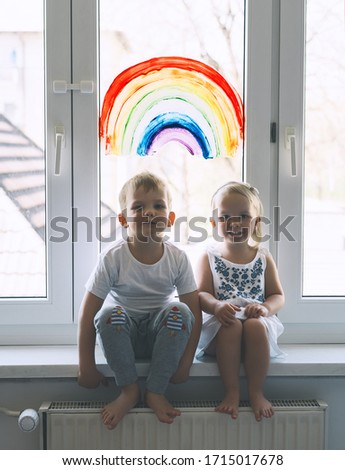 Cute little children on background of painting rainbow on window. Photo of kids leisure at home, childcare, safety joy symbol, family life. Brother and sister on vacation. #1715017678