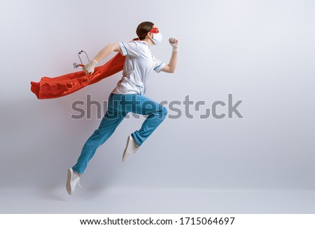 Doctor wearing facemask and superhero cape during coronavirus outbreak. Virus and illness protection, quarantine. COVID-2019. Super hero power for  medicine. Royalty-Free Stock Photo #1715064697