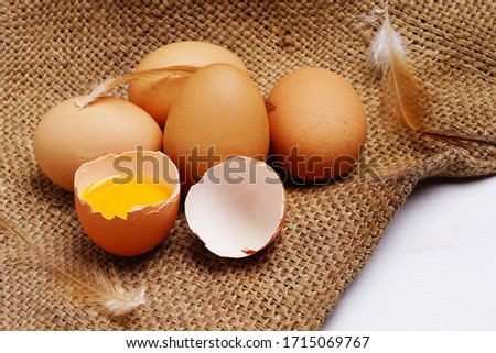 brown chicken eggs in egg carton and egg yolk with chicken feather on hemp sack background. copy space. Natural healthy food and organic farming concept. Eggs in box #1715069767