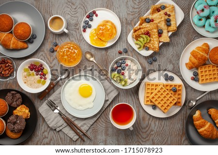Continental breakfast captured from above (top view, flat lay). Coffee, tea, croissants, jam, egg, pancakes, maffins and oatmeal. Wooden background. Family breakfast table. #1715078923