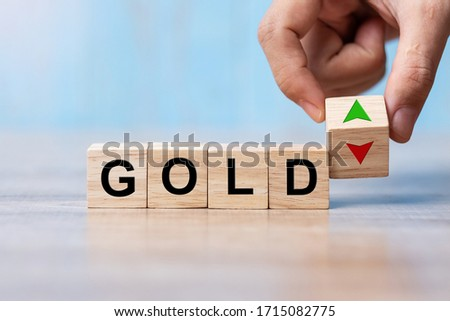 business man Hand change wood cube block with GOLD text to UP and Down arrow symbol icon. Interest rate, stocks, financial, cut loss and economic concept
