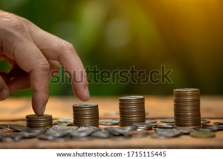 Coins a men's hand  placed and sorted coins on a wooden board. #1715115445